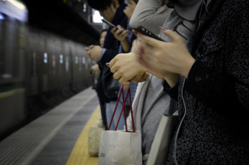 Midsection of people using mobile phone while standing on railroad station platform
