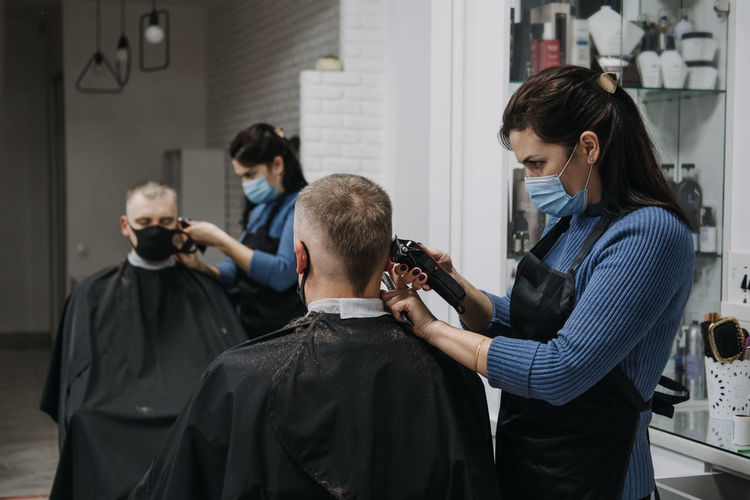 Female barber cutting hair of customer in saloon