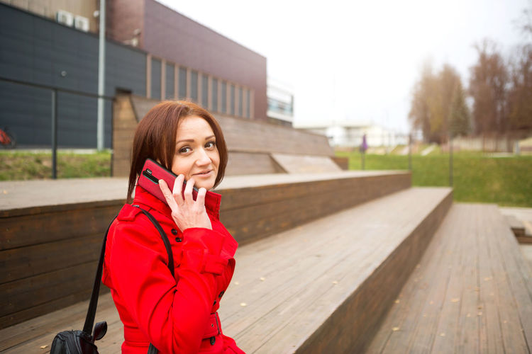 Portrait of woman standing on mobile phone in winter