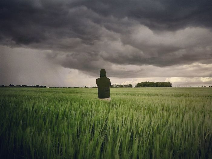 Rear View Of Man Standing On Field Against Cloudy Sky