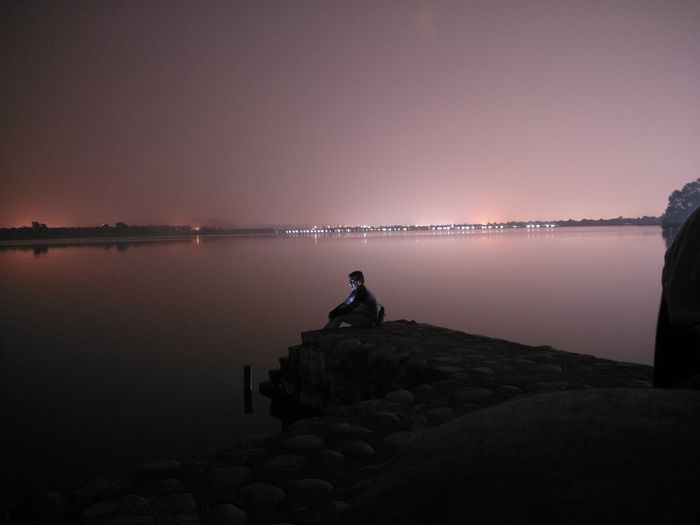 Man sitting by lake on rock at night