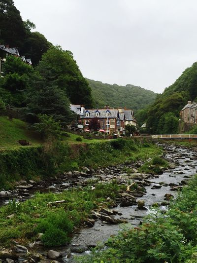 Stream flowing by mountain at lynmouth