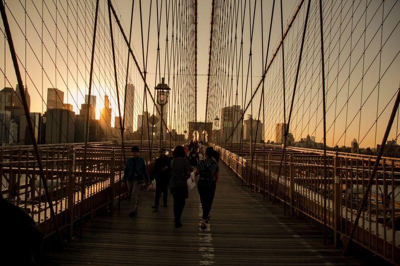 People walking on footbridge in city against sky