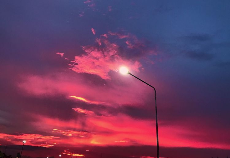 Low angle view of illuminated street lights against dramatic sky