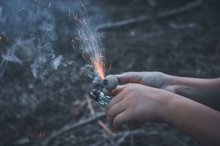 Cropped hands burning firework over field