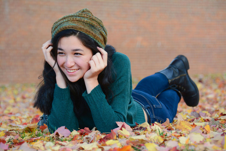Smiling woman lying on field during autumn at park