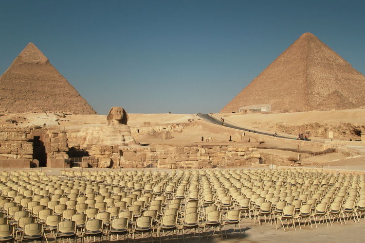 Empty chairs by sphinx and pyramid of khafre against clear sky