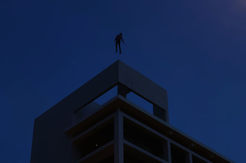 Low angle view of silhouette building against clear blue sky