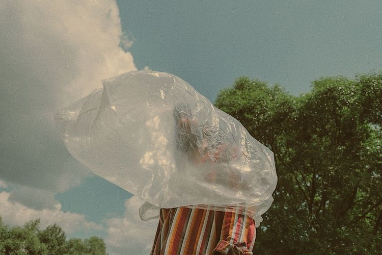 Man Wearing Plastic Bag Against Sky