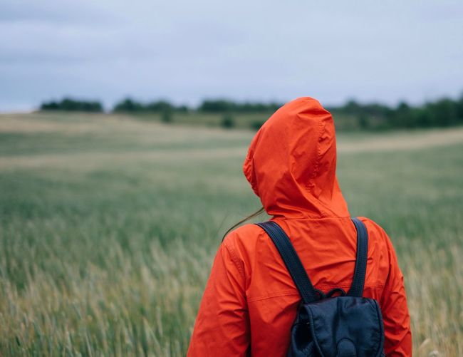 Rear view of woman wearing hood and backpack while looking at field