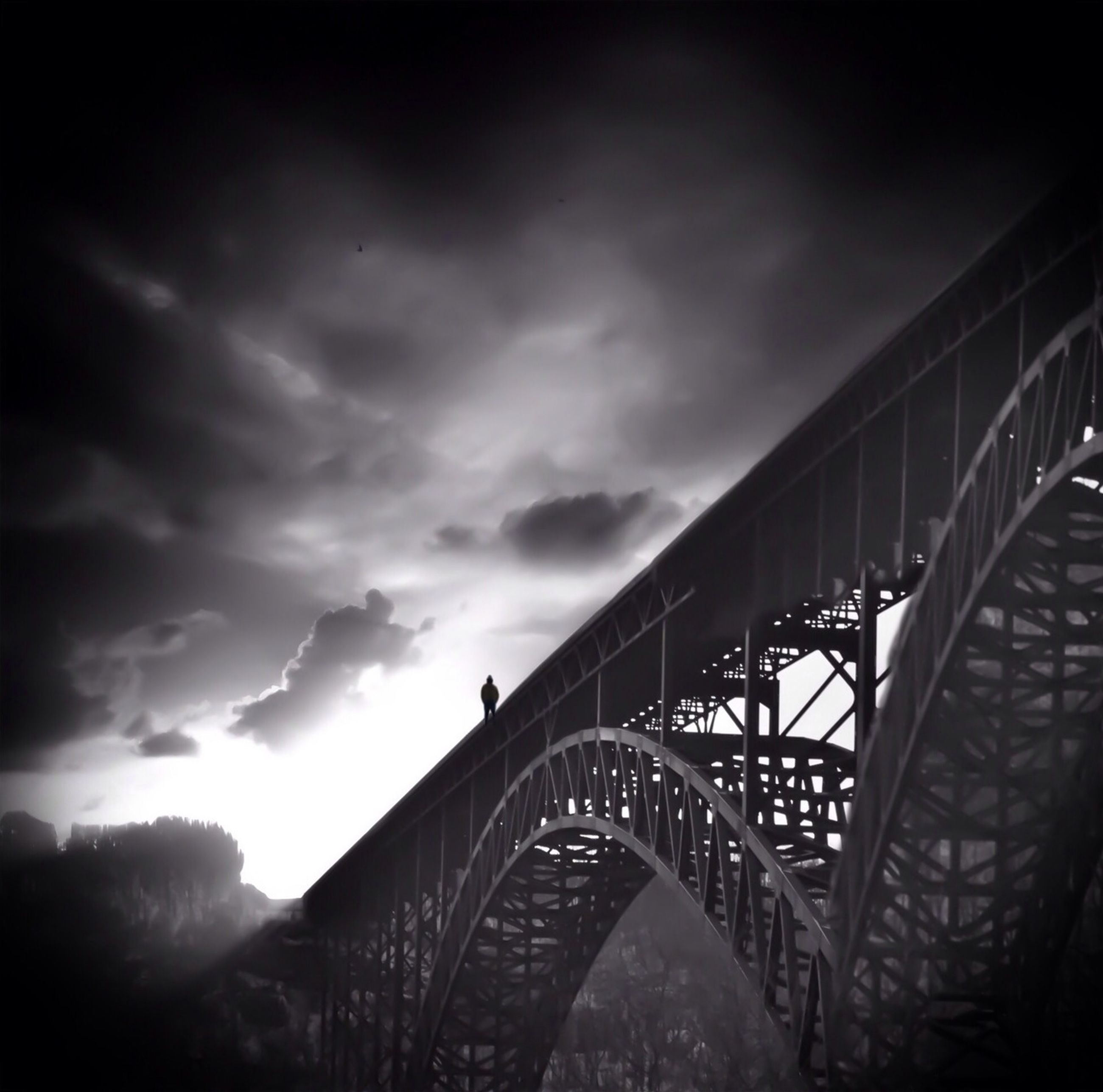 sky, built structure, architecture, bridge - man made structure, cloud - sky, low angle view, connection, transportation, cloudy, engineering, cloud, bridge, railing, silhouette, dusk, outdoors, overcast, railway bridge, day, metal