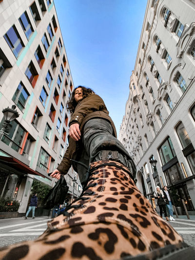 Low angle view of man against buildings in city