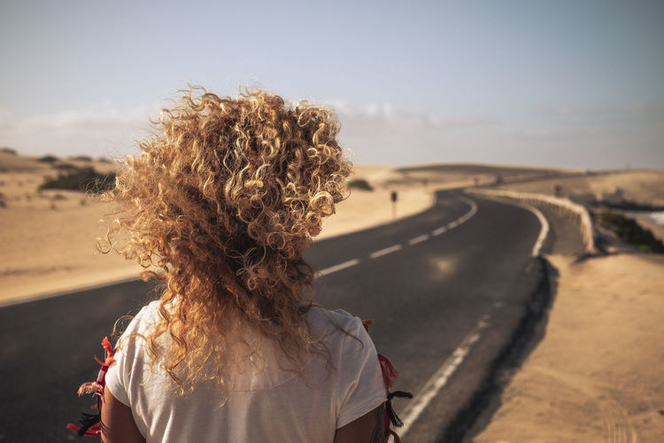 Rear view of woman with curly hair standing on road against sky