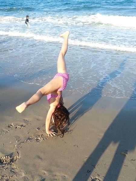 Young girl doing gymnastics on the beach. Beachphotography Young Girl Playing On The Beach Gymnastics Enjoying Life Balance And Composure Balance