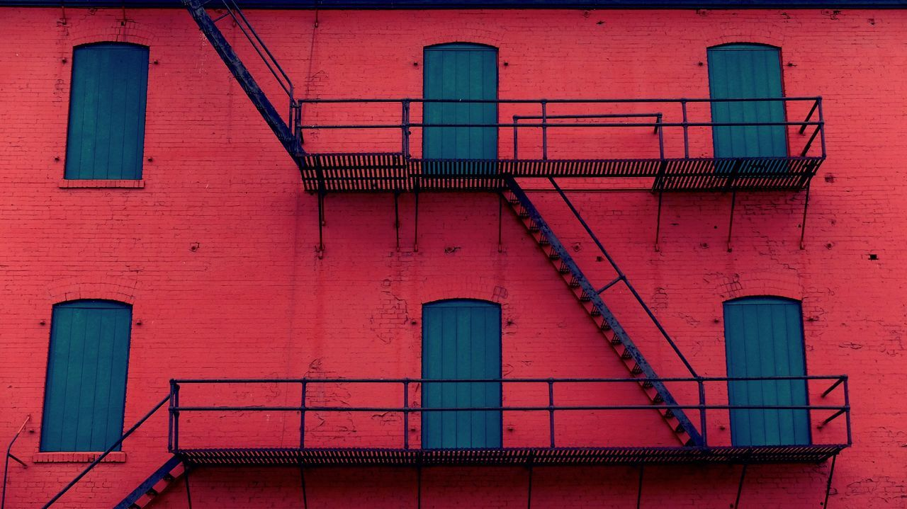 Low Angle View Of Steps And Windows On Red Building