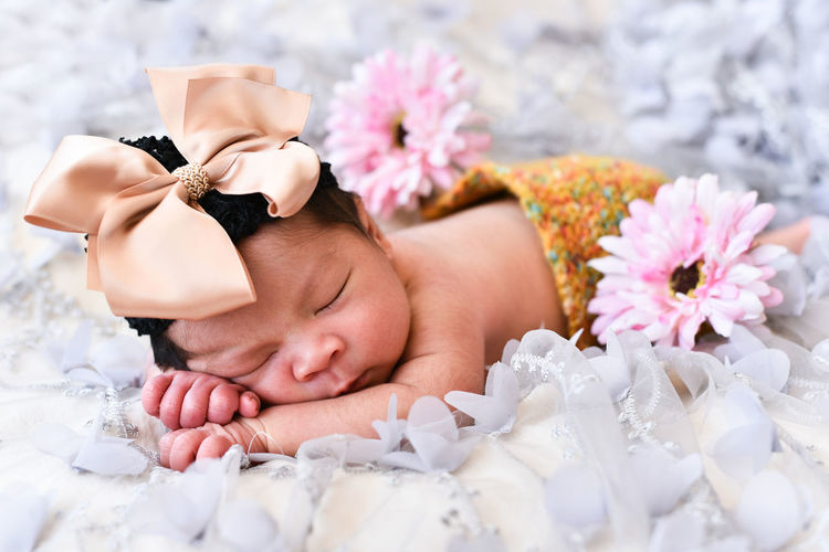 Close-up of cute baby girl with flowers sleeping on bed