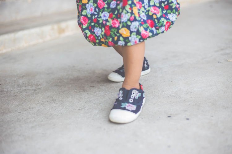Low section of girl walking on footpath