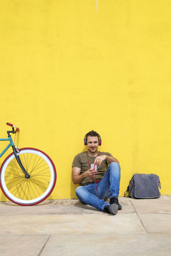 Front view of an attractive guy sitting on the floor with trendy look, using a mobile phone having headphones while looking at screen against a yellow wall One Person Sitting Casual Clothing Young Adult Full Length Young Men Yellow Looking At Camera Wall - Building Feature Real People Copy Space Smiling Lifestyles Front View Portrait Bicycle Transportation Leisure Activity Flooring Jeans Young Man Hipster Trendy T-shirt Males  Man PhonePhotography Sitting Headphones Wall Mobile Phone Smartphone Using Phone Listening To Music Bike Fixie