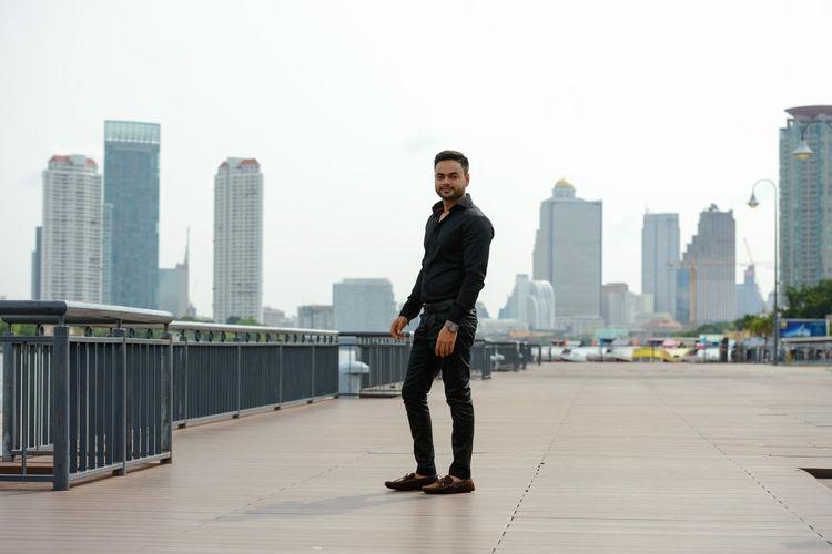 Full length portrait of man standing on railing against buildings in city