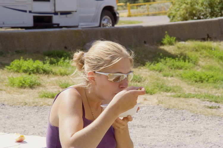 Close-up of young woman having food while sitting outdoors
