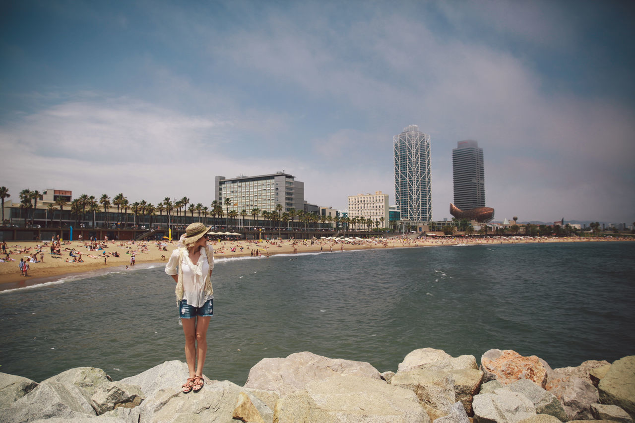 architecture, real people, built structure, building exterior, sky, water, city, lifestyles, leisure activity, rear view, sea, one person, casual clothing, outdoors, full length, cloud - sky, standing, skyscraper, day, cityscape, beach, women, young adult, nature, young women, urban skyline, beauty in nature, people