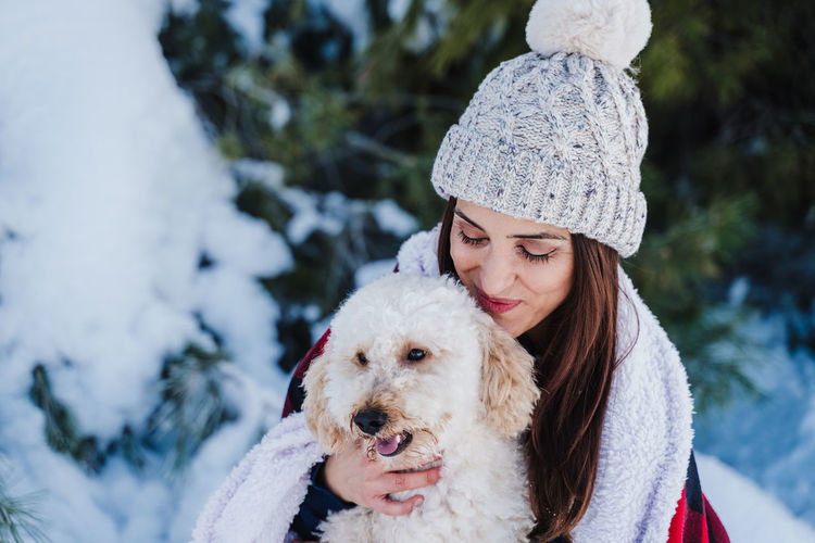 Woman with dog in snow during winter