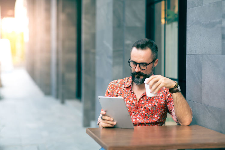 Man using digital tablet while sitting at table