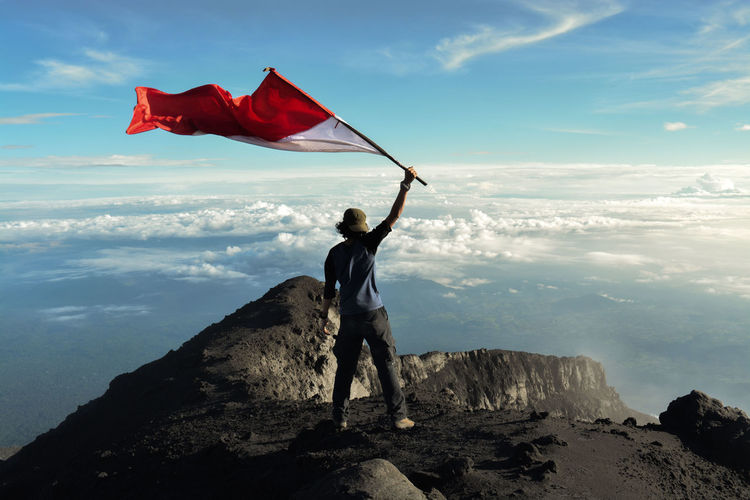 Rear view of man standing on rock with indonesian flag against sky