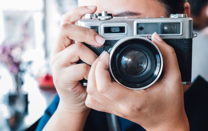 Close-up of woman holding camera