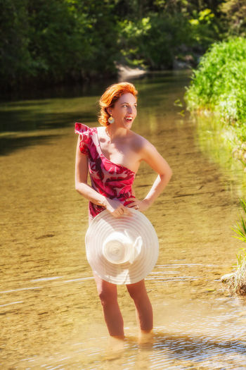 Smiling woman looking away while standing in water