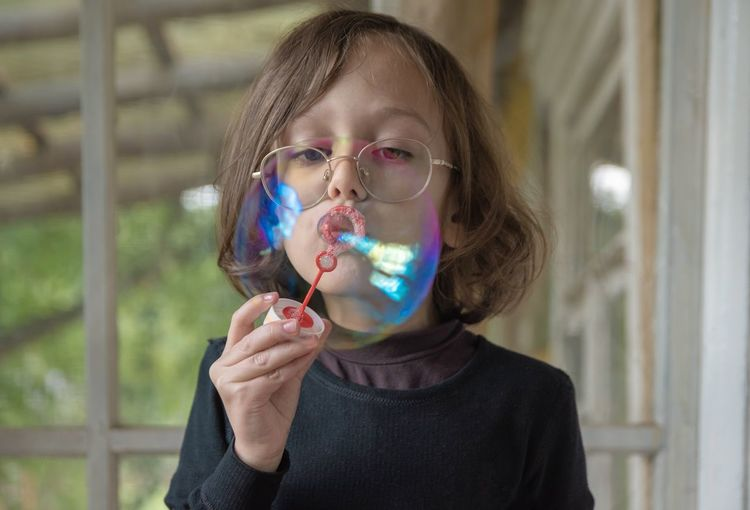 Close-up of boy blowing bubble at home