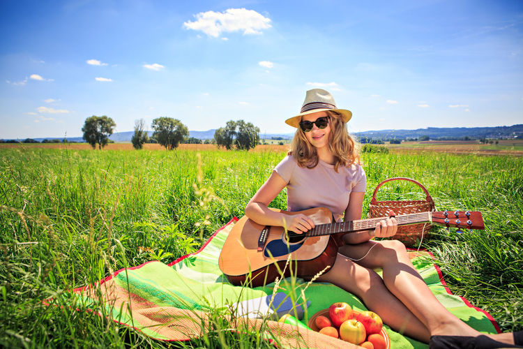 Outdoor portrait of young girl with a guitar Fashion Field Girl Glasses Grass Guitar Land Leisure Activity Lifestyles Music Musical Instrument Nature One Person Outdoors Plant Portrait Real People Sitting Sky Sunglasses Teenager Women Young Adult Young Women