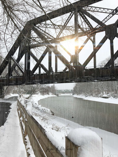 Bridge over river against sky during winter