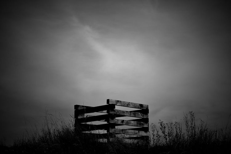 Low Angle View Of Wooden Structure In Field Against Cloudy Sky