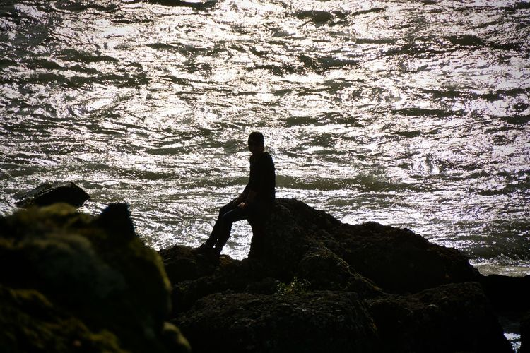 Silhouette woman sitting on rock by water