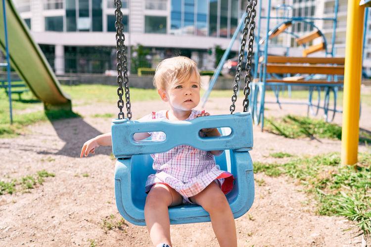 Full length of boy sitting on slide at playground