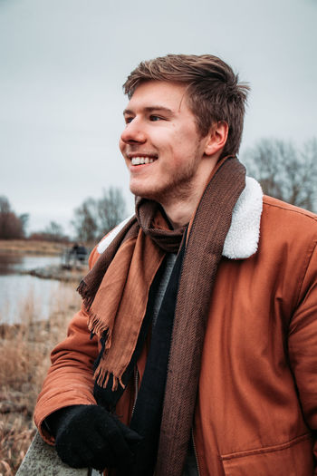Smiling young man looking away while standing against sky
