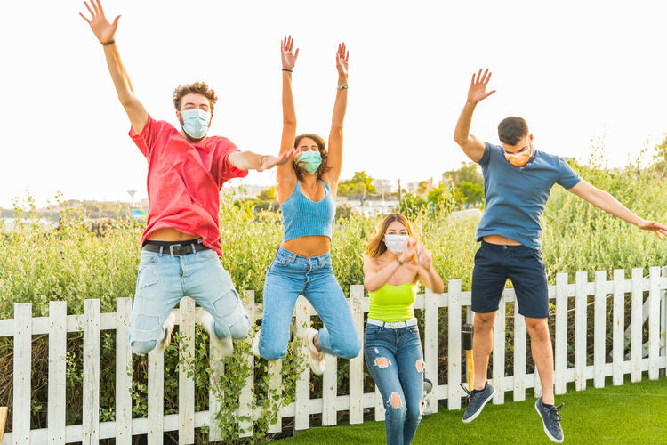 Group of people jumping outdoors