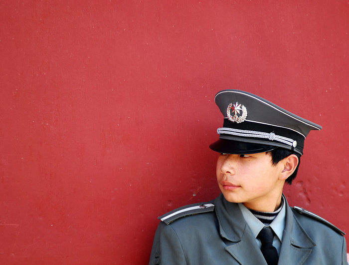 A very young guard can barely fill his uniform in spite of the woolen sweater underneath the shirt and tie, while he rests against a red wall in the Forbidden City Forbidden City Uniform Working Candid Clothing Copy Space Guard Headshot Kid Lifestyles Mid Adult Occupation One Person Portrait Real People Red Wall Standing Uniform Uniform Cap Wall - Building Feature Young Adult Young Man
