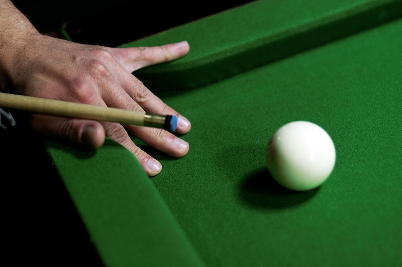 Cropped Image Of Man Playing Pool At Table