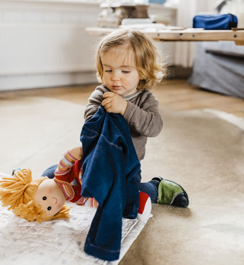 Cute Child Playing With Doll On Rug At Home