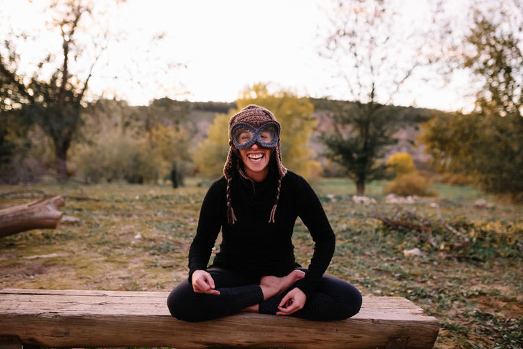 Portrait of smiling woman wearing knit hat sitting on bench at park