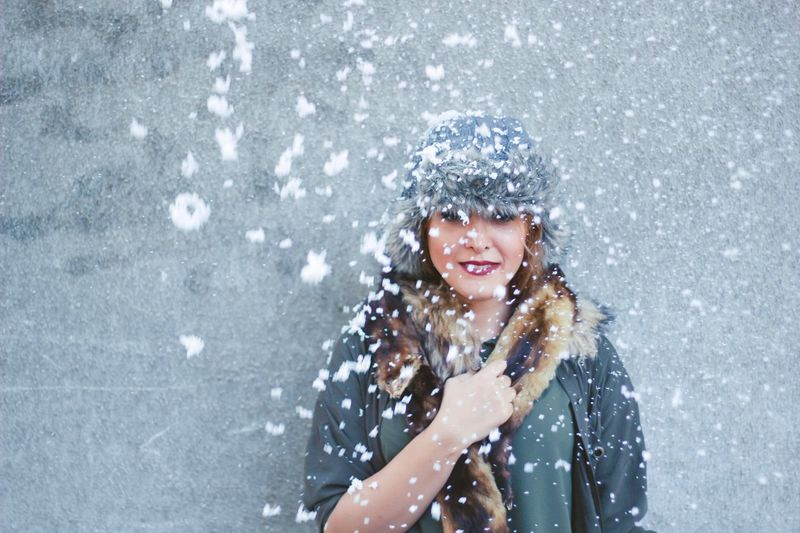 Snow falling against woman standing by wall