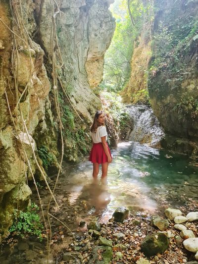 Woman standing on rock by waterfall in forest