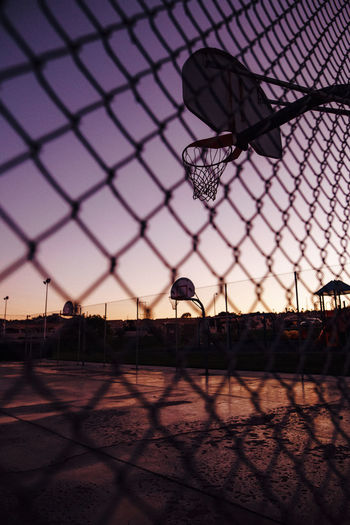 Silhouette basketball hoop seen through chainlink fence against sky during sunset