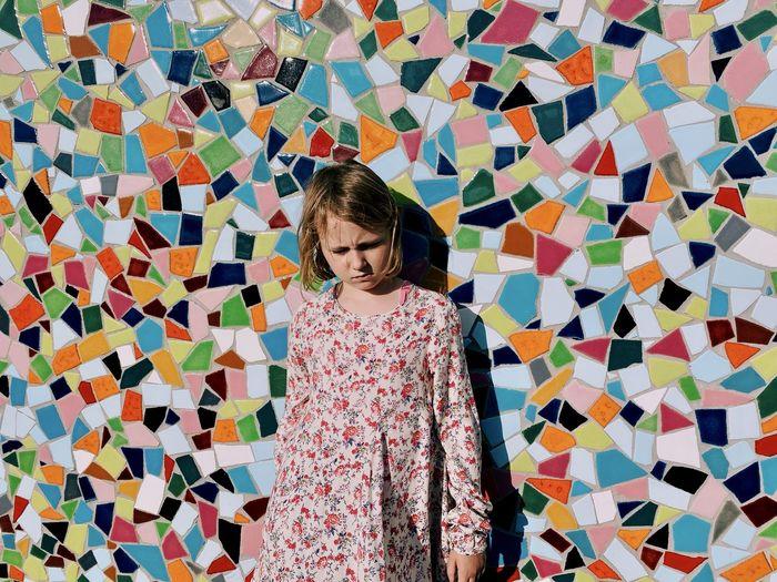 Full length of girl standing against multi colored wall
