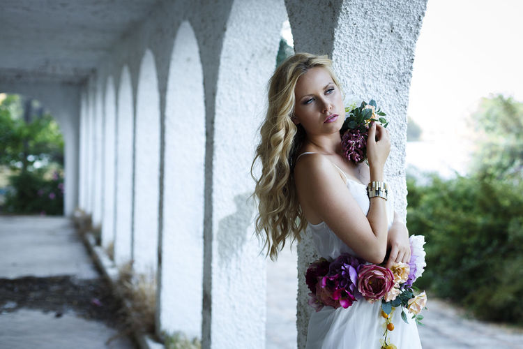 Young blond female with blue eyes standing at the porch. Attractive girl with an intent and serene look wearing a romantic white dress and flowers Adult Architectural Column Beautiful Woman Beauty Contemplation Day Fashion Flower Flowering Plant Focus On Foreground Hair Hairstyle Lifestyles Long Hair One Person Outdoors Plant Real People Standing Women Young Adult Young Women