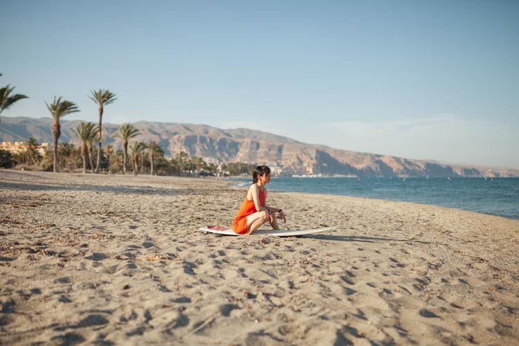 Full length of man sitting on sand at beach against sky