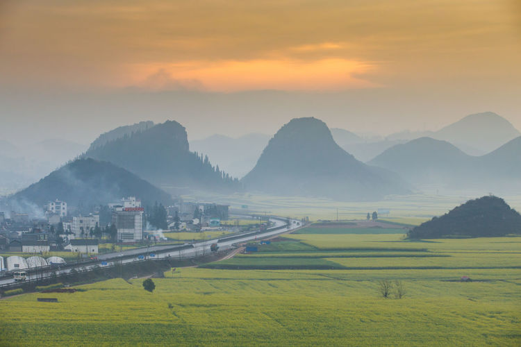Mountain Sky Scenics - Nature Beauty In Nature Mountain Range Sunset Environment Landscape Tranquil Scene Nature Architecture Tranquility Cloud - Sky Grass Field Built Structure Land Fog Idyllic No People Outdoors