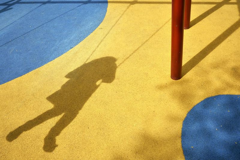 Shadow Of Person On Playground Swing